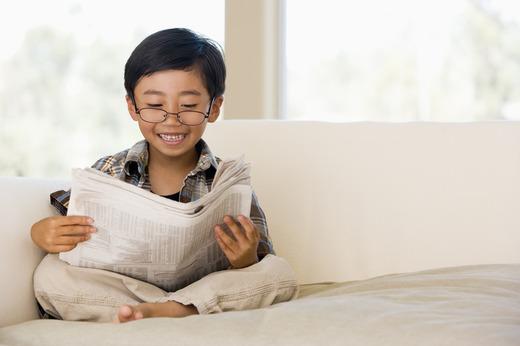 Gutt i sofa leser avis